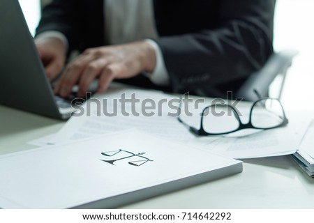 Lawyer working in office. Attorney writing a legal document with laptop computer. Glasses on table. Pile of paper with scale and justice symbol. Law firm and business concept. Foto stock ©