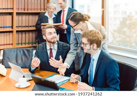 Lawyers in their law firm working on computer with books in background Foto stock ©