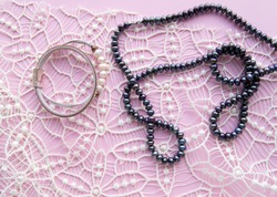 Lay Flat pink background and the gorgeous lace, glittering necklace of black pearls, and stylish bracelet. Beauty and fashion concept