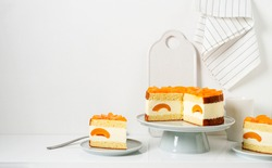 Layered cheesecake with peaches on cake stand, white background.