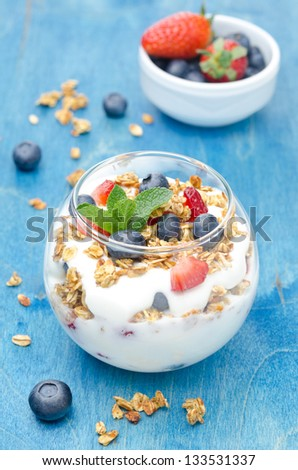 layered dessert with yogurt, granola, fresh berries and a bowl of berries on a blue background vertical