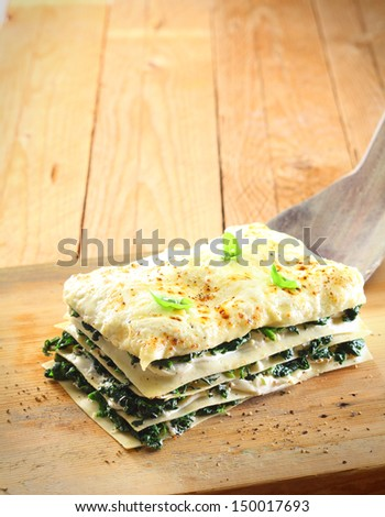 Layered spinach and cheese lasagne on a wooden board for a nutritious vegetarian meal
