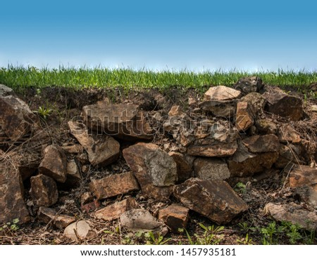 layers of ground from grass to stones, big stones and earth in a slice #1457935181