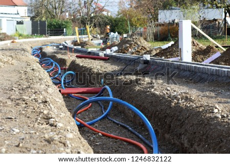 Laying a fiber optic cable for fast internet, Electricity and telephone cable along a new street. Cable Installation power lines at city street, industrial electricity and communication concept. #1246832122