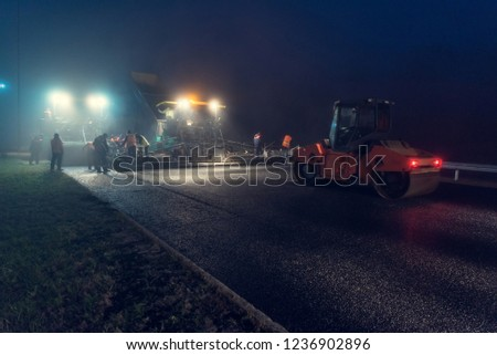 Laying asphalt paver at night with headlights. Road construction. #1236902896