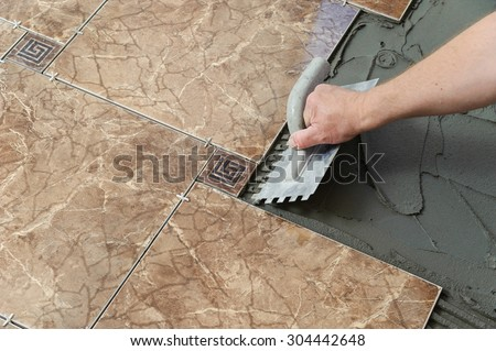 Laying Ceramic Tiles. Troweling adhesive onto a concrete floor in preparation for laying white floor tile.