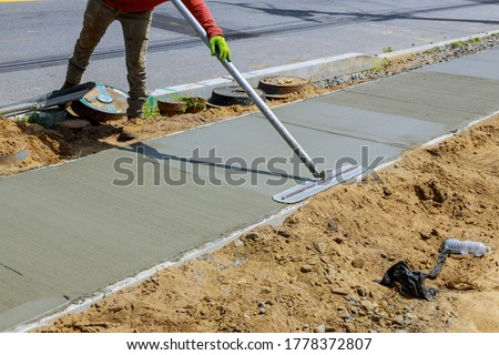 Photo of  Laying down new sidewalk in wet concrete on freshly poured sidewalks