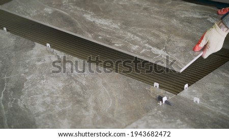 Laying floor ceramic tile. Renovating the floor. Construction workers laying tile over concrete floor using tile levelers, notched trowels and tile mortar. Foto stock ©