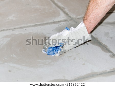 Laying floor tiles, tiler cleaning tiles after filling up joints
