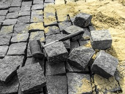 Laying granite paving stones - building background with copy space. A black rubber mallet lies among gray rectangular blocks of natural stone on the background of yellow sand