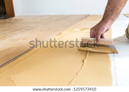 Laying hardwood parquet. Putting glue on the floor.