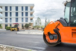 laying of asphalt pavement near the new building, asphalt rollers in operation for the improvement of the territory of the city