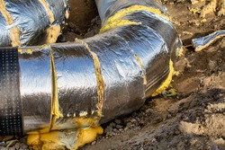 Laying of heating large diameter pipeline in the trench. Main district pipeline diverting.