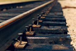 Laying of new railway tracks with wooden sleepers laid on groundwork crushed stone. Railway industry and transport infrastructure.