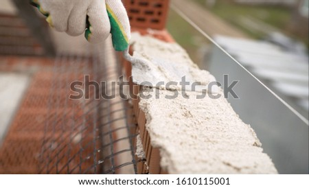 Laying of red bricks. Profesional worker builds an expensive red brick house