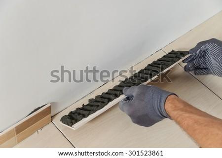 Laying the tiles. Tiler sticks border tiles