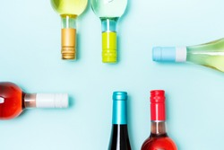 Layout frame of foil caps in different bright colors of white and rose wine bottles on blue background with copy space. Minimal abstract colorful mockup concept of alcohol beverage. Flat lay.
