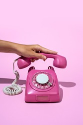 Layout made of pink telephone on blue background. Retro vintage 60's and 70's aesthetic with summer shadows. Flat lay.