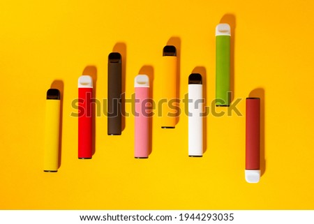 Layout of colorful disposable electronic cigarettes with shadows on a yellow background. The concept of modern smoking, vaping and nicotine. Top view Stock photo ©