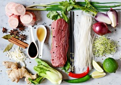 Layout of products on Vietnamese Pho Bo soup on gray   background. Traditional Vietnamese Pho bo soup with herbs, meat, rice noodles, broth.