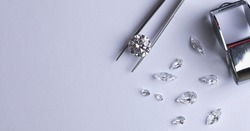 Layout of round cut diamond on tweezers with other diamonds of different cuts on light background with copy space top view.
