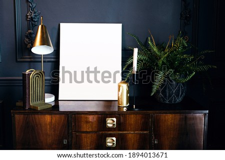 layout of the photo frame in a modern stylish interior, designer accessories table lamp and book holder. a golden candle and green house plants on a vintage wooden table. Stock photo ©