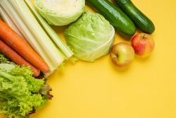 layout of vegetables on a yellow background: carrots, celery, cucumbers, zucchini, apples, cabbage, lettuce. The concept of healthy eating. Vegan and vegetarian concept. Top view, place for text