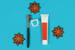 Layout top view of toothpaste, brush, vampire teeth and spider webs in Halloween style on a blue background. Medicine, health, holidays concept