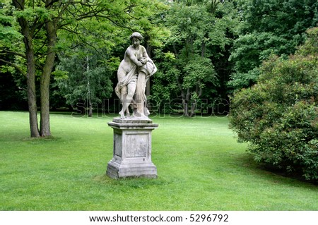 Lazienki - Royal Park in Warsaw, Poland. Green lawn, trees and a classical statue.