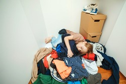 Lazy boy sleeping on the pile of thrown clothes. Mess in open wardrobe. Untidy clutter clothing closet. Boy with messy stack of clothes things on floor. Home chores housework.