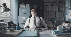 Lazy exhausted businessman sitting at office desk and sleeping, he is snoring with his mouth open