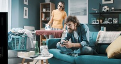 Lazy husband playing videogames and relaxing on the sofa while his wife is doing household chores, gender inequality concept