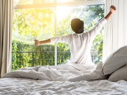 lazy man happy waking up in the bed rising hands to window in the morning with fresh feeling relax
