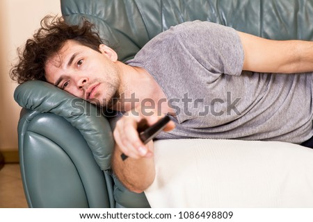 Lazy man with the remote on the couch Сток-фото ©