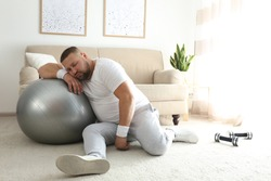 Lazy overweight man with sport equipment sleeping on floor at home