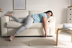 Lazy overweight woman resting on sofa at home