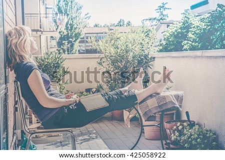 lazy - relaxed blond woman reading, falling asleep in balcony on a warm summer day - custom vintage colors fading and haze effects