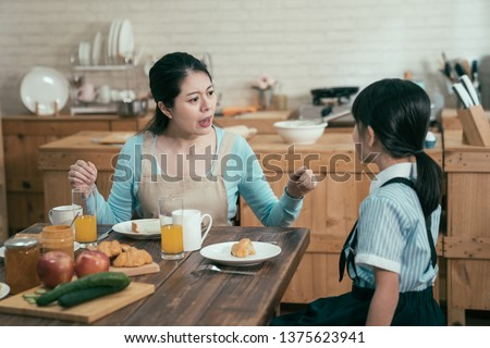 lazy sleepy little girl wake up late for school sitting at kitchen table with breakfast at home. frowning angry mom loudly nag at daughter bad habit in early morning. unhappy asian mother worried. #1375623941