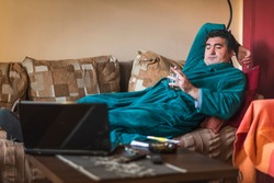 Lazy, sluggish mature man drinking whiskey in the morning, laying on his sofa and watching some online videos on his laptop