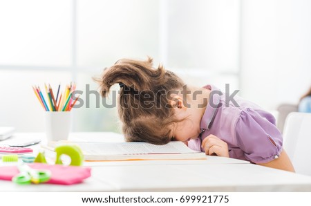 Lazy student girl at home, she is resting with her face down on the school book, education and childhood concept