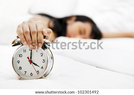 Lazy woman sleeping with hand covering an alarm clock in front