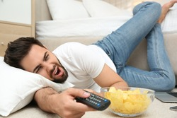 Lazy young man with bowl of chips watching TV while lying on floor at home