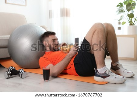Lazy young man with smartphone eating junk food on yoga mat at home Сток-фото ©