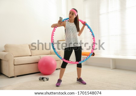 Lazy young woman with hula hoop and smartphone at home