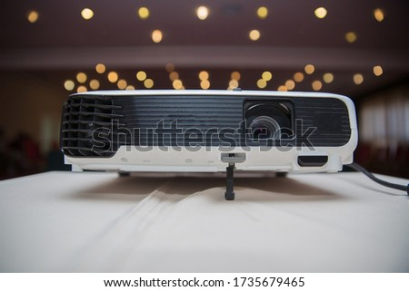 LCD Projector technology video presentation and home Entertainment object . mini led projector on wood table in a room projector home theater idea and concept . Close up projector in conference room .