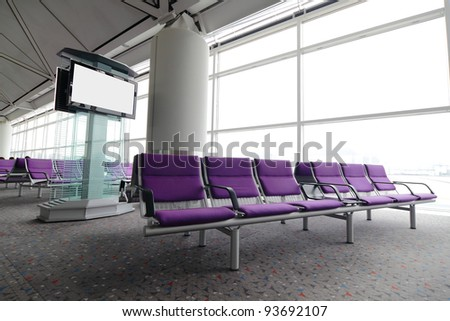 LCD TV and row of purple chair at airport