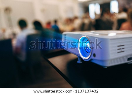 LCD video projector at business conference or lecture in office with copy space. projector on ceiling indoors.