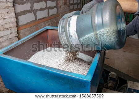 LDPE or HDPE polyethylene granules are poured for melting into new plastic bags. Production of plastic bags from recycled garbage. White granules are poured into the extruder.