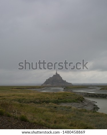 Le Mont Saint Michel, an UNESCO world heritage site in France on a sundown. View of the castle from the field. Medieval city and abbey on the mountain of the same name, surrounded by yellowing #1480458869