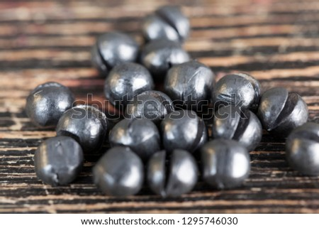Lead sinker for fishing rods during fishing, close-up of round sinkers on a black board #1295746030
